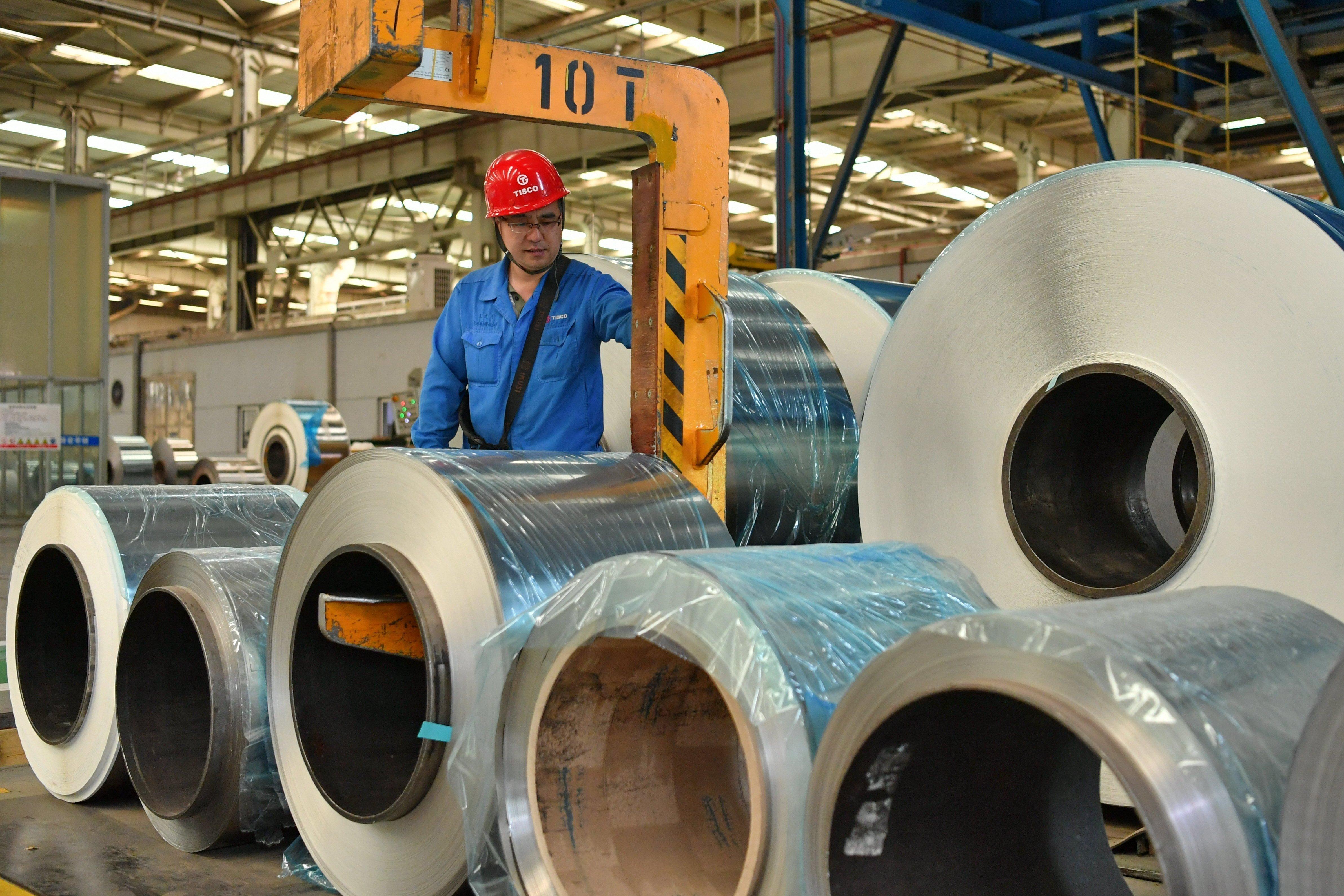 太钢集团员工在操控超薄带状不锈钢的移动设备(5月24日摄)。新华社记者 曹阳 摄.JPG